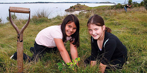 Two young girls planting trees on Motuihe Island